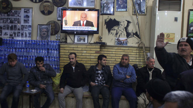 """Kurdish patrons sit in a local cafe as TV broadcasts a speech by Iraq's Sunni Vice President Tariq al-Hashemi in Sulaimaniyah, 260 kilometers (160 miles) northeast of Baghdad, Iraq, Monday, Feb. 20, 2012. al-Hashemi slammed government charges that he ran death squads as politically motivated and called on """"all honest Iraqi people"""" to rise up in his defense. (AP Photo/Yahya Ahmed)"""