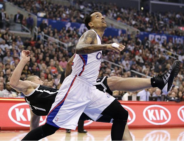 Los Angeles Clippers' Matt Barnes, front, fouls Brooklyn Nets' Mason Plumlee during the first half of an NBA basketball game on Saturday, Nov. 16, 2013, in Los Angeles