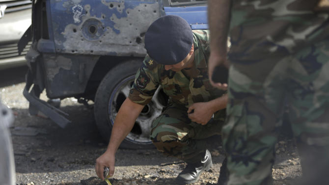 A Lebanese army officer investigates part of a rocket which struck a car exhibit on a street at the Mar Mikhael district, south of Beirut, Lebanon, Sunday May 26, 2013. Rockets slammed Sunday into two Beirut neighborhoods that are strongholds of Lebanon's Hezbollah group, wounding at least 4 people, Lebanese security officials and media said. Tensions have been running high in Lebanon, and Syrian rebels have threatened to retaliate against the militant Shiite Hezbollah group for sending fighters to assist President Bashar Assad's forces in Syria. (AP Photo/Hussein Malla)