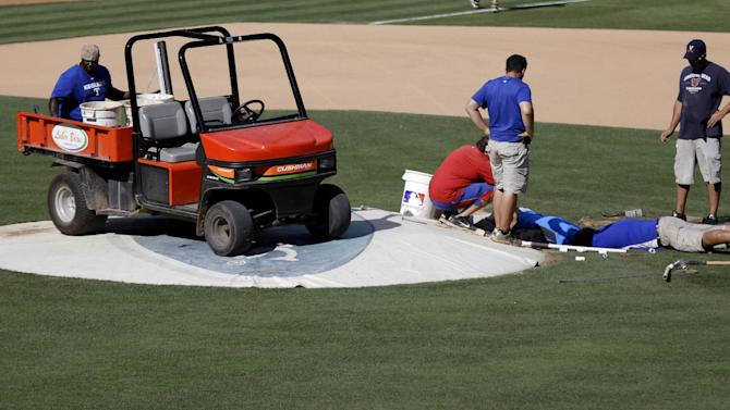 The grounds crew works to repair a sinkhole next to the pitcher's mound made by a busted pipe under the infield before the baseball game between the Cleveland Indians and Texas Rangers Tuesday, June 11, 2013, in Arlington, Texas. On-field batting practice was canceled for both teams while workers tried to fix the problem  before the night's scheduled game. (AP Photo/LM Otero)