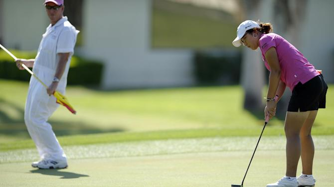 Lydia Ko, right, of New Zealand, and her caddie Patrick Boyd react to a near-miss putt on the first hole during the third round of the LPGA Kraft Nabisco Championship golf tournament in Rancho Mirage, Calif. Saturday, April 6, 2013. (AP Photo/Rodrigo Pena)