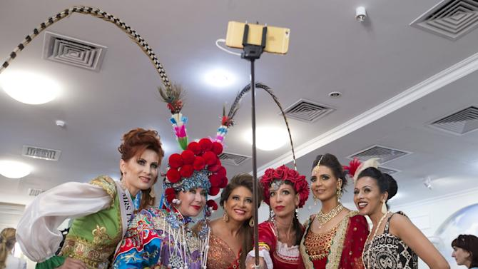 "Participants take a photo with a smartphone on a selfie stick as they wait backstage before the ""Mrs Universe 2015"" contest in Minsk"