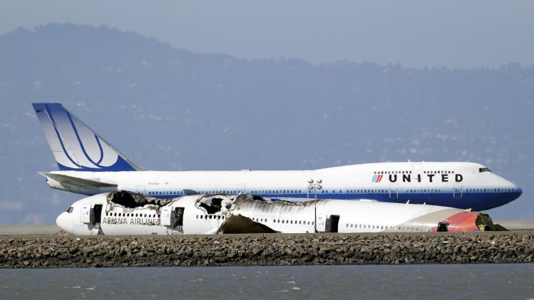 A United Airlines plane readies for take off next to the wreckage of Asiana Flight 214 at the San Francisco International Airport in San Francisco, Sunday, July 7, 2013. (AP Photo/Marcio Jose Sanchez)