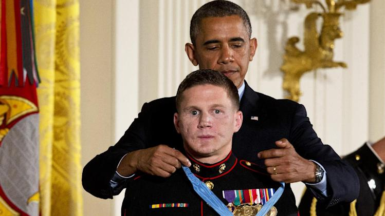"President Barack Obama awards retired Marine Cpl. William ""Kyle"" Carpenter, the Medal of Honor for conspicuous gallantry, Thursday, June 19, 2014, during a ceremony in the East Room of the White House in Washington. Carpenter received the Medal of Honor for his courageous actions while serving as an Automatic Rifleman in Helmand Province, Afghanistan. (AP Photo/Jacquelyn Martin)"