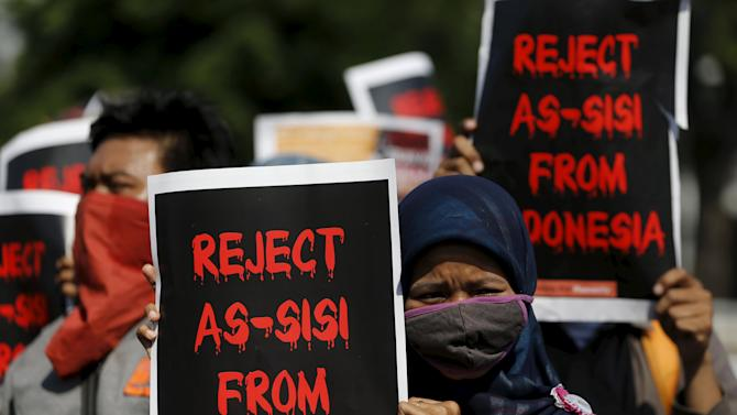 Protesters hold posters during a demonstration against visiting Egyptian President Abdel-Fattah el-Sissi in Jakarta