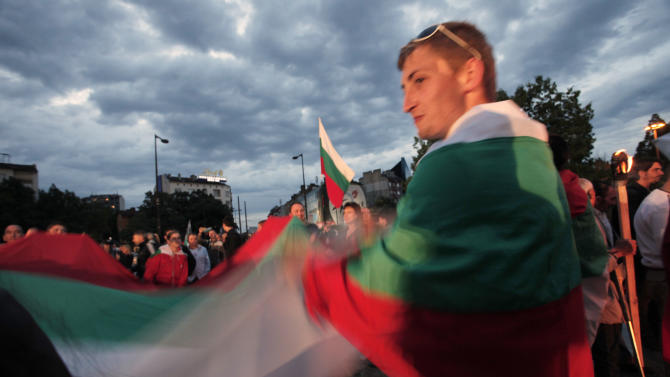 Protesters wave Bulgarian flag during a protest claiming the current parliamentary elections are not legitimate in Sofia, Sunday, May 12, 2013. Bulgarians voted Sunday in parliamentary elections with no party expected to win a majority to form a government, fueling fears about more political and economic instability in the country. (AP Photo/Valentina Petrova)