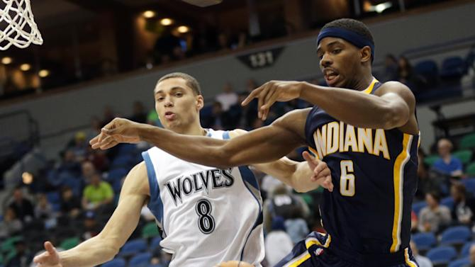 Minnesota Timberwolves' Zach LaVine, left, and Indiana Pacers' C.J. Fair go airborne for the loose ball in the second half of a preseason NBA basketball game, Tuesday, Oct. 21, 2014, in Minneapolis. The Timberwolves won 107-89. (AP Photo/Jim Mone)