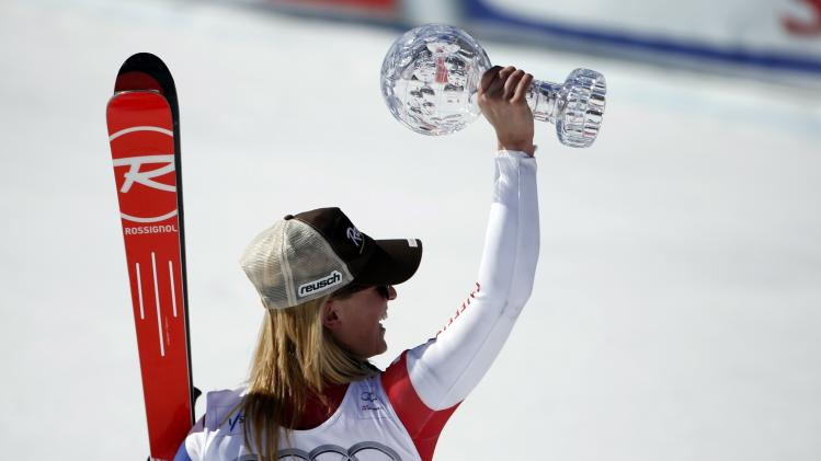 Gut of Switzerland celebrates with the trophy after winning the overall women's Super G competition during the FIS Alpine Skiing World Cup finals in the Swiss ski resort of Lenzerheide