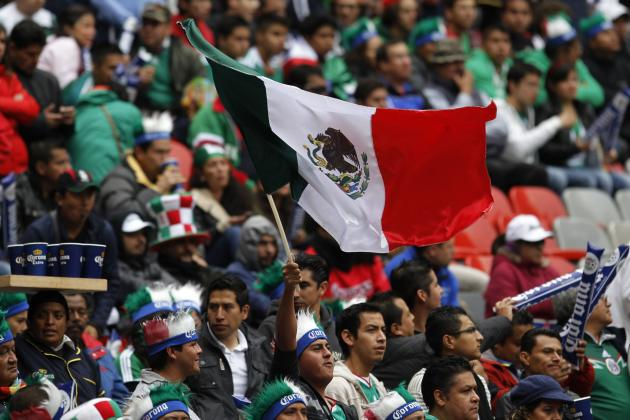 A Mexico fan waves the national flag before the 2014 World Cup qualifying playoff first leg soccer match between Mexico and New Zealand at Azteca stadium in Mexico City