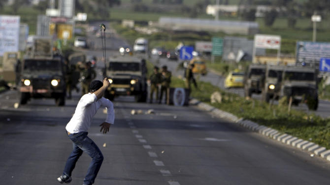 A Palestinian man throws stones at Israeli soldiers during clashes after a rally  in support of the Palestinian prisoners in Israeli jails, north of the West Bank city of Jenin, Sunday, Feb. 24, 2013. The death of a 30-year-old Palestinian after interrogation by Israel's Shin Bet security service stokes new West Bank clashes, along with Israeli fears of a third Palestinian uprising. (AP Photo/Mohammed Ballas)