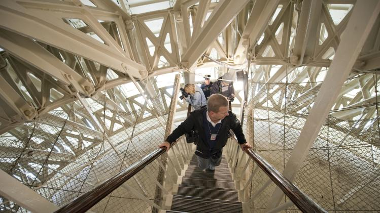 Members of the media climb stairs through the infrastructure holding up the ceiling of the rotunda within the US Capitol dome during a media tour on Capitol Hill in Washington
