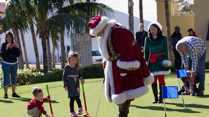 """Blake Ballard, 3, left, and his sister Carina, 6, take lesson on miniature golf from Santa Claus and his elves during the Macy's National Santa Tour at the The Ritz Carlton Golf Resort in Naples, Fla., Friday, Dec. 21, 2012. Santa made the stop at the resort to see ten Make-A-Wish children and their families as part of the Macy's national tour. Now in its fifth year, Macy's """"Believe campaign invites children to mail letter to Santa using Macy's Santa Mail letterboxes. Macy's donates a dollar for each letter mailed in store up to $1 million, to Make_A-Wish. (Erik Kellar/AP Images for Macy's)"""