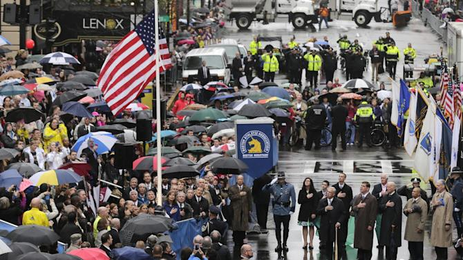 Survivors, officials, first responders and guests pause as the flag is raised at the finish line during a tribute in honor of the one year anniversary of the Boston Marathon bombings, Tuesday, April 15, 2014 in Boston. (AP Photo/Charles Krupa)