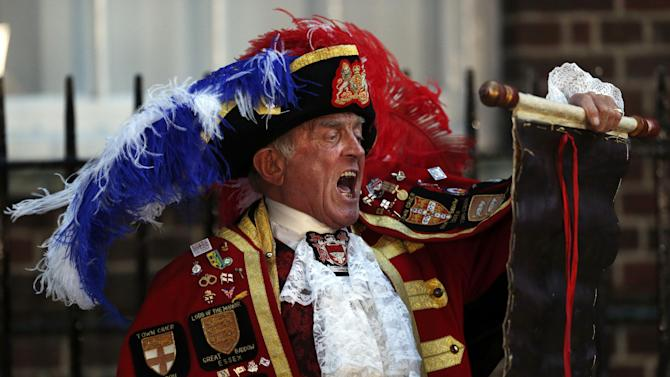 FILE - In a Monday, July 22, 2013 file photo, Tony Appleton, a town crier, announces the birth of the royal baby, outside St. Mary's Hospital exclusive Lindo Wing in London. Well-wishers waiting outside St. Mary's Hospital in London might have been forgiven for thinking Appleton had the royal seal of approval. Appleton is in fact a crier, but in Romford, a commuter town just east of London, and in Bury St. Edmunds, a market town in southeastern England, not Buckingham Palace. In an interview Wednesday, July 24, he acknowledged that he had no official royal role, but simply showed up in costume after getting a tipoff that the Duchess of Cambridge had given birth. Confused American journalists identified him as a bona fide mouthpiece for Buckingham Palace.(AP Photo/Lefteris Pitarakis, File)