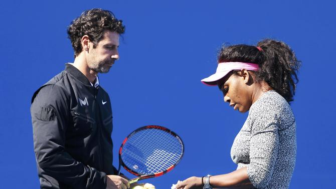 Williams of the U.S. talks to her coach Patrick Mouratoglou during a practice session before her women's singles final match against Sharapova of Russia at the Australian Open 2015 tennis tournament in Melbourne