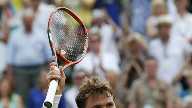 Stan Wawrinka of Switzerland waves to fans after winning his match against Victor Estrella Burgos of Dominican Republic at the Wimbledon Tennis Championships in London