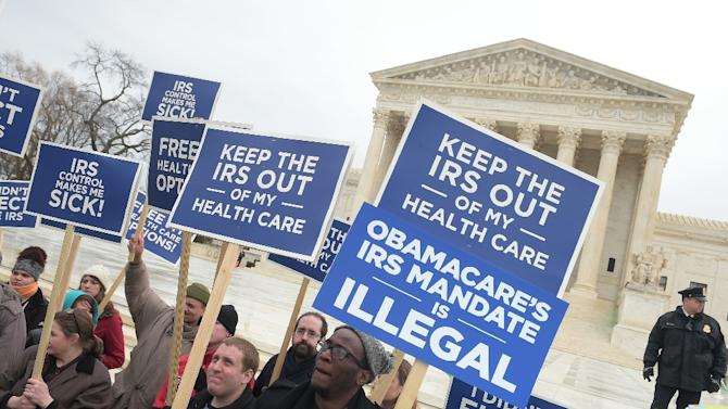 """Protestors hold placards challenging """"Obamacare"""" outside of the US Supreme Court on March 4, 2015, in Washington, DC"""