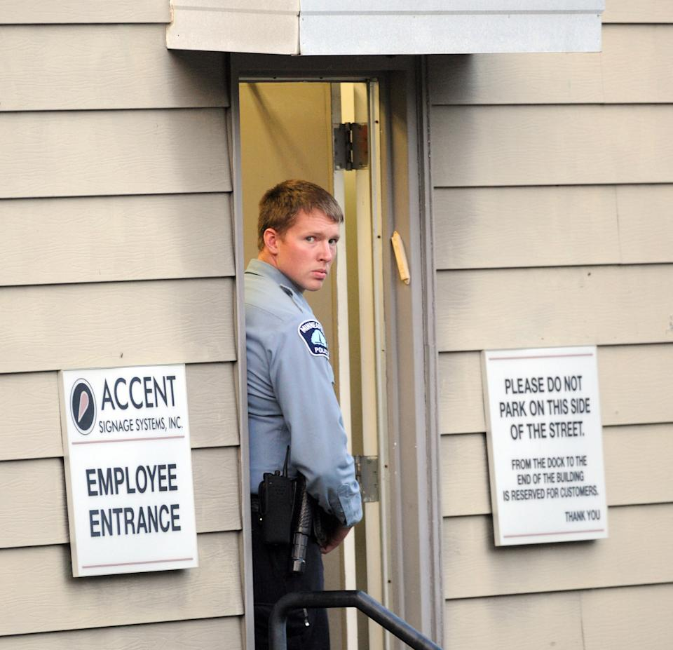 "A Minneapolis police officer stands at the entrance of Accent Signage Systems as police investigate a shooting at the business that police say left ""several"" people dead, including the shooter, who was found dead from a self-inflicted gunshot wound, Thursday, Sept. 27, 2012 in Minneapolis.  (AP Photo/Craig Lassig)"