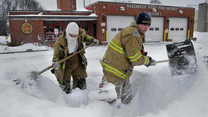Junior firefighter Adam Krach, left, and firefighter Steve Ellis of the Warehouse Point Fire Department dig snow from a hydrant outside their station in East Windsor, Conn. on Saturday, Feb. 9, 2013. A behemoth storm packing hurricane-force wind gusts and blizzard conditions swept through the Northeast overnight. (AP Photo/Jessica Hill)