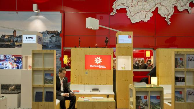 A man sits at Switzerland's stand at the International Tourism Trade Fair (ITB) in Berlin