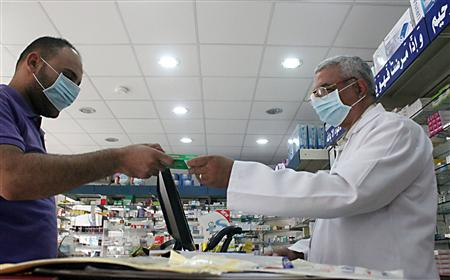 A man, wearing a surgical mask as a precautionary measure against the novel coronavirus, pays for medicine at a hospital pharmacy in Khobar city