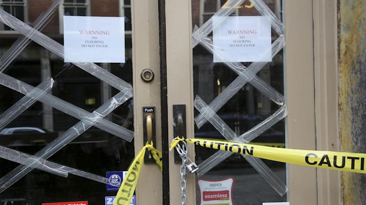 In this Thursday, Feb. 7, 2013 photo, caution tape and signs warn that Barbarini restaurant on Front St. in New York has no flooring.  Nearly four months after Superstorm Sandy hit, the historic cobblestone streets near the water's edge in lower Manhattan are eerily deserted, and among local business owners, there is a pervasive sense that their plight has been ignored by the rest of Manhattan. (AP Photo/Mary Altaffer)