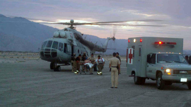 In this image released by the Mexican Navy on Monday July 4, 2011, an injured man who survived after a boat capsized is prepared to be taken into an ambulance after being rescued by the Navy in the town of San Felipe, Mexico Monday July 4, 2011. A U.S. tourist died after a fishing boat capsized in an unexpected storm in the Gulf of California off the Baja California peninsula and of the 44 people on the boat, seven U.S. tourists remain missing along with one Mexican crew member, the Mexican navy said. (AP Photo/SEMAR)