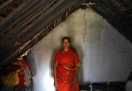 Palaniamma, 40, a housewife, poses for a photograph inside her mud-and-thatch home at the village Krishnapuram in Dharmapuri district in the southern Indian state of Tamil Nadu June 21, 2013. Thomson Reuters Foundation/Mansi Thapliyal