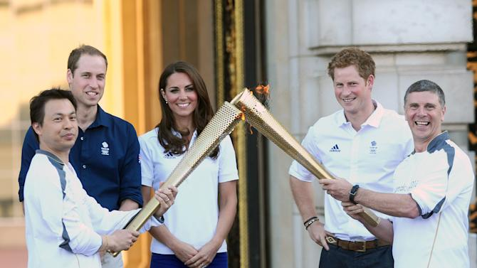 Prince William and his wife Kate, the Duke and Duchess of Cambridge, and Prince Harry are joined by children from the Team Britain Ambition Program as they watch Wai Ming hand over the London 2012 Olympic Torch to John Hulse during a visit to Buckingham Palace in London, on Day 69 of the London 2012 Olympic Torch Relay on Thursday, July 26, 2012. (AP Photo/Ian West, PA) UNITED KINGDOM OUT; NO SALES; NO ARCHIVE