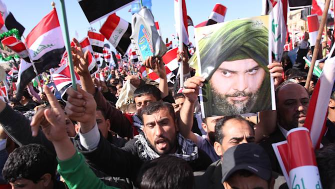 Followers of Shiite cleric Muqtada al-Sadr chant anti-Iraqi Government slogans and wave Iraqi flags during a protest in Basra, Iraq's second-largest city, 550 kilometers (340 miles) southeast of Baghdad, Iraq, Monday, March 19, 2012. Followers of the anti-American Shiite cleric Muqtada al-Sadr, seen in the poster, are demanding better living conditions in Iraq on the ninth anniversary of the U.S.-led invasion of their country . (AP Photo/Nabil al-Jurani)