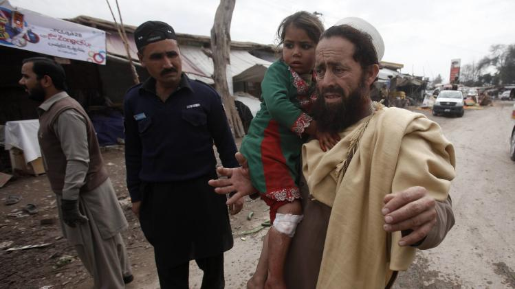 A resident carries his daughter, who was injured in a bomb blast, as they evacuate site of bomb blast on outskirts of Peshawar