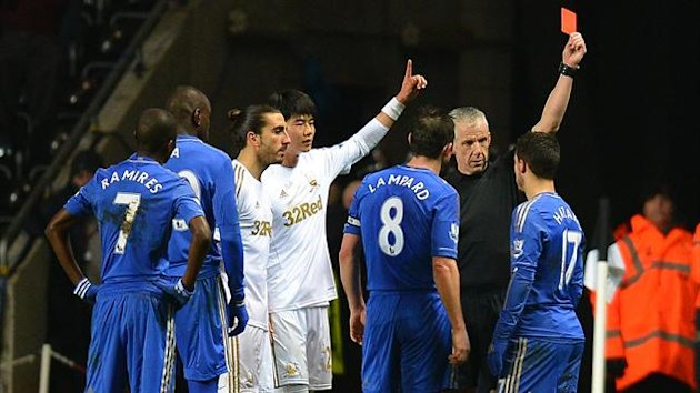Chelsea&#39;s Belgium midfielder Eden Hazard (R) is sent off by referee Chris Foy after an incident involving a ballboy during the English League Cup semi-final second leg football match between Swansea City and Chelsea at The Liberty stadium (AFP)