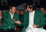 Bubba Watson (R) of the US shakes hands with 2011 Masters champion Charl Schwartzel of South Africa during the awards ceremony following his victory in the 76th Masters golf tournament in a play-off against Louis Oosthuizen of South Africa at Augusta National Golf Club in Augusta, Georgia