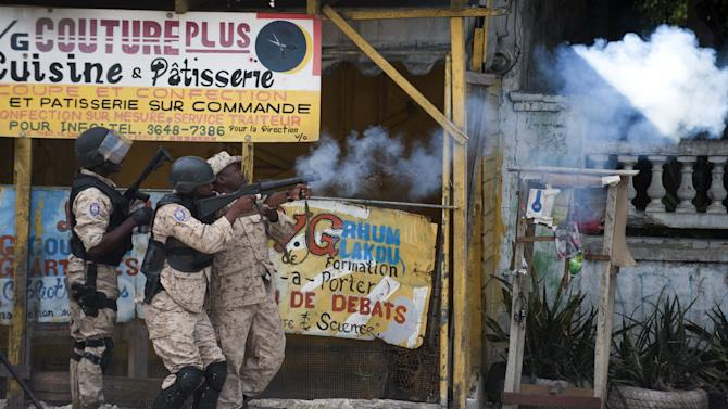 Haitian police fire tear gas during clashes after a march against the government of President Michel Martelly in Port-au-Prince, on February 4, 2015