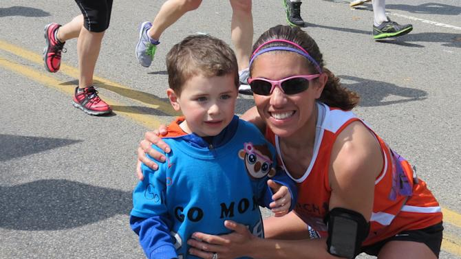 "This Monday, April 15, 2013 photo provided by Mark Fratto shows his wife, runner Courtney Fratto, and their son Gavin, 3, at mile 20 during the Boston Marathon in Boston. Fratto finished the race just seconds before the first bomb exploded. When the bomb went off just after she crossed the finish line, she ran for safety instead of to the injured. Fratto, a nurse who is the coordinator of intestinal transplants in the Pediatric Transplant Center at Boston Children's Hospital, wishes she could have reacted the way a number of others did. ""I could see there was mass casualties,"" she said. ""I have this very horrible guilt that I didn't run and help them.'' (AP Photo/Mark Fratto)"