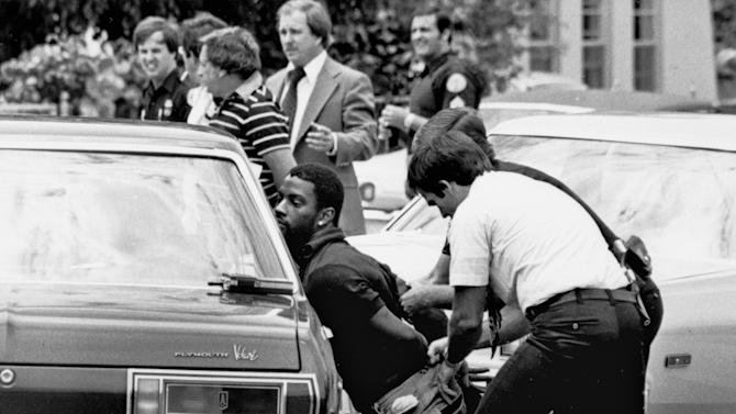 """FILE - In this May 18, 1979 file photo, police handcuff a suspect during a drug raid in Miami. Police said eight were arrested and marijuana was seized. On the occasion of  """"Legalization Day,"""" Thursday, Dec. 6, 2012, when Washington's new law takes effect, AP takes a look back at the cultural and legal status of the """"evil weed"""" in American history. (AP Photo/Al Diaz, File)"""