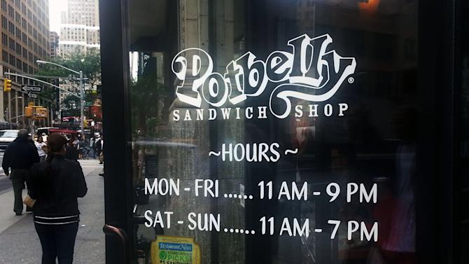 FILE - In this Friday, Sept. 27, 2013, file photo, people walk past a Potbelly Sandwich shop in New York. Shares of sandwich maker Potbelly more than doubled in their Nasdaq trading debut and the company's stock soared $18.90 to $32.90 in morning trading Friday, Oct. 4, 2013. (AP Photo/Tali Arbel, File)