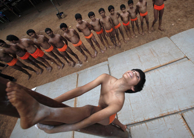 A boys perform a Mallakhamb pose on a pole as others watch at the Shree Samartha Vyayam Mandir in Mumbai