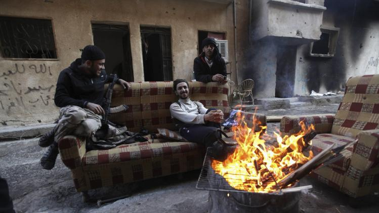 Free Syrian Army fighters sit around fire along a street in Deir al-Zor, eastern Syria