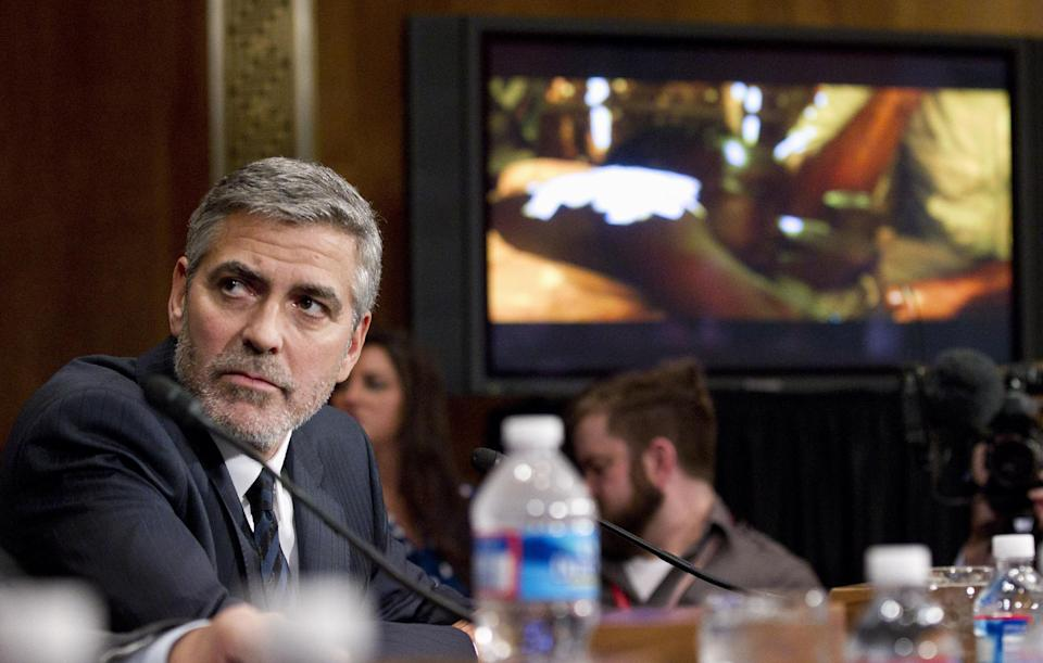 Actor George Clooney watches a video from his recent trip to Sudan as he testifies on Capitol Hill in Washington, Wednesday, March 14, 2012, before the Senate Foreign Relations Committee hearing on Sudan.  (AP Photo/Manuel Balce Ceneta)