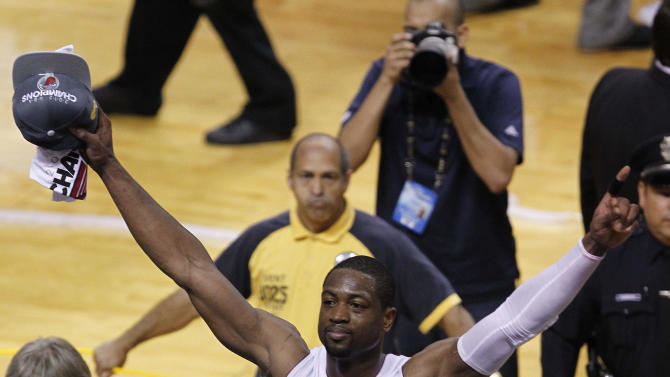 The Miami Heat's Dwyane Wade (3) raises his arms in victory after Game 5 of the NBA finals basketball series against the Oklahoma City Thunder, Thursday, June 21, 2012, in Miami. The Heat won 121-106 to become the 2012 NBA Champions. (AP Photo/Wilfredo Lee)