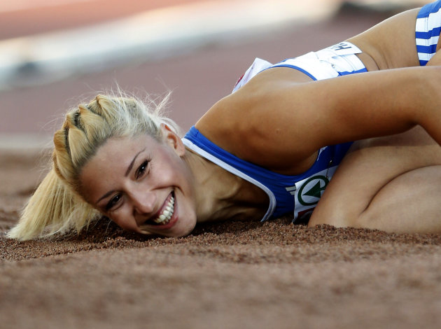 "FILE- Greece's Voula Papachristou lands in the sand after her jump at the Women's Triple Jump final at the European Athletics Championships in Helsinki, Finland, in this file photo dated Friday, June 29, 2012. The Hellenic Olympic Committee has removed triple jumper Voula Papachristou from the team taking part in the upcoming London Olympic Games over comments she made on twitter making fun of African immigrants and expressing support for a far-right party. ""The track and field athlete Paraskevi (Voula) Papachristou is placed outside the Olympic Team for statements contrary to the values and ideas of the Olympic movement,"" a statement by the Hellenic Olympic Committee says. Papachristou is in Athens, and was to travel to London ""shortly before the track events start,"" the announcement says.(AP Photo/Matt Dunham, file)"