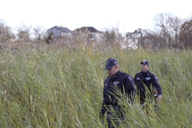 Police officers wearing wet suits leave a site where the body of a 2-year-old child killed during Superstorm Sandy was discovered in Staten Island, New York, Thursday, Nov. 1, 2012. Brandon Moore, 2,