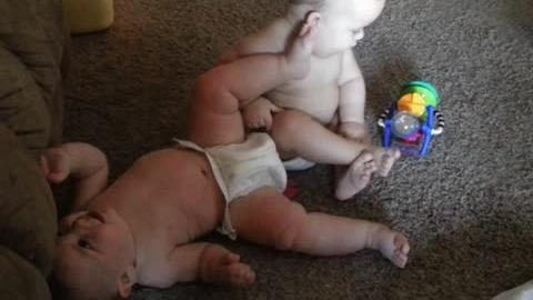 Adorable Baby Kicks Twin Brother Over