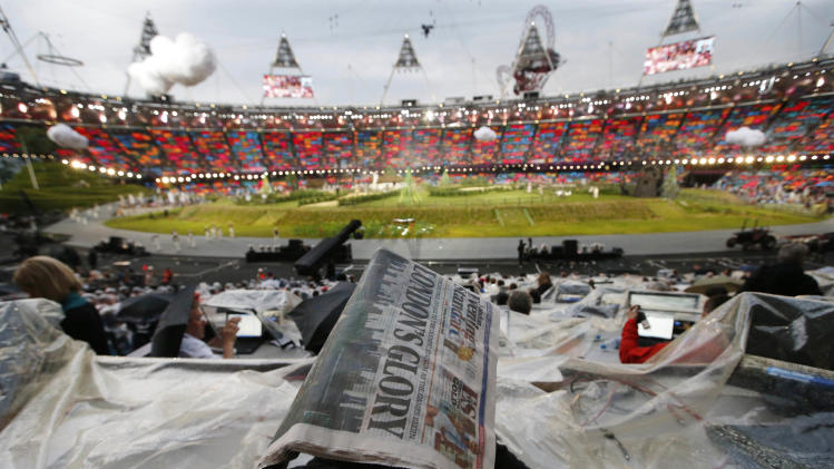 A member of the media covers himself with a newspaper during a rain shower ahead of the Opening Ceremony at the 2012 Summer Olympics, Friday, July 27, 2012, in London. (AP Photo/Jae C. Hong)
