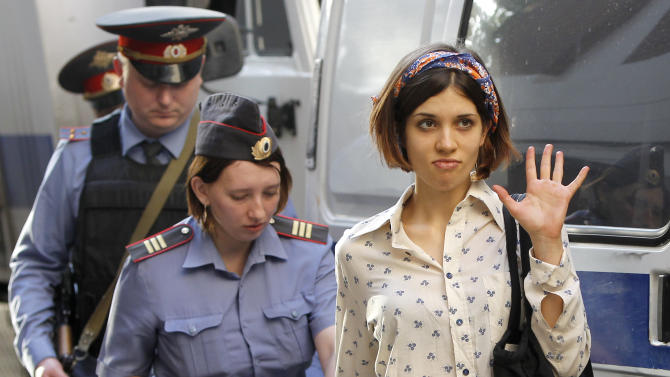 """Nadezhda Tolokonnikova, right, a member of feminist punk group Pussy Riot is escorted to a police van in Moscow, Russia, Wednesday, Aug. 1, 2012. Tolokonnikova and two other members of the group are facing trial on charges of hooliganism for performing a """"punk prayer"""" at Moscow's main cathedral against Vladimir Putin's return to the Russian presidency. (AP Photo/Misha Japaridze)"""