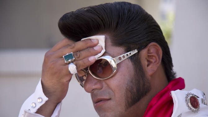 "Elvis impersonator Cristian Morales wipes sweat from his brow while standing out on The Strip posing for photos with tourists, Thursday, June 27, 2013 in Las Vegas. Morales preferred to stand out in the 112 degree heat of the day instead of working the cooler evening hours saying ""We'd much rather fight with the sun than fight with the drunk people."" A high pressure system parking over the West is expected to bring temperatures this weekend and into next week that are extreme even for a region used to baking during the summer. (AP Photo/Julie Jacobson)"