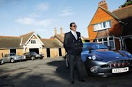 Actor Roger Moore, with a collection of Aston Martin cars