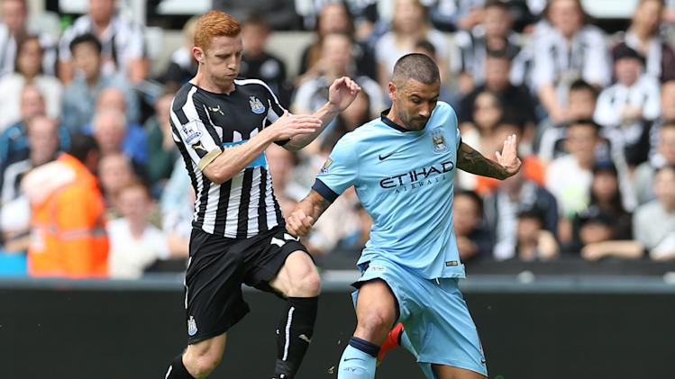 Newcastle United's Jack Colback (left) challenges Manchester City's Aleksandar Kolarov during the English Premier League match at St James' Park in north east England, on August 17, 2014