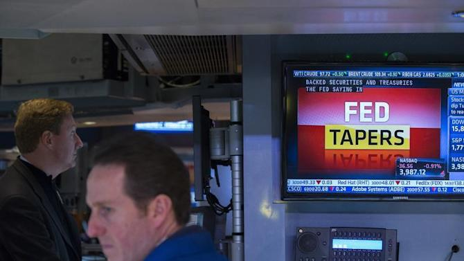 Traders listen to an announcement by the U.S. Federal Reserve on the floor of the New York Stock Exchange in New York